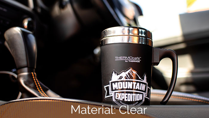 Thermos travel mug in a car with a white and clear sticker applied to the side of the mug