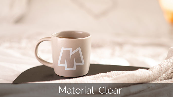 A lovely warm mug of coffee on a bed side table with a white and clear sticker applied to the mug