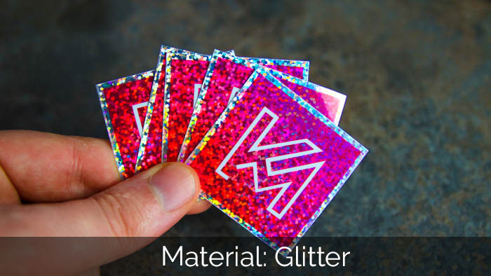 Some pink square KM glitter stickers in a hand