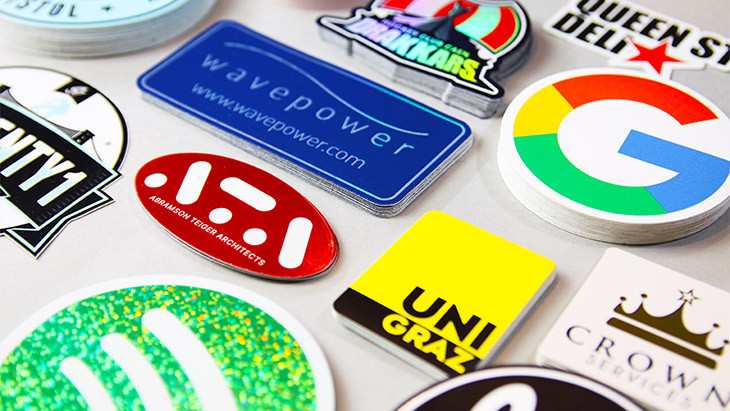 Piles of logo stickers from brands including google on a grey background