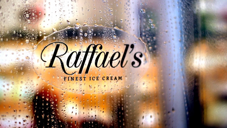 Raffael's oval clear sticker applied to a transparent window with water droplets running over the surface of the sticker