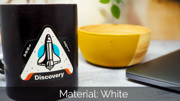 A die cut white vinyl sticker on a black mug