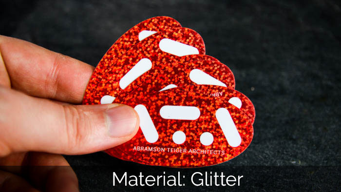 A pile of oval ATA red glitter stickers in a hand