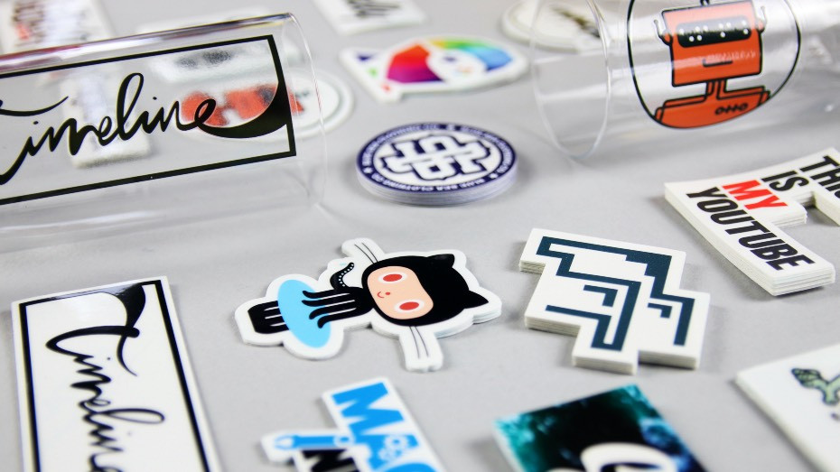Many custom printed transparent stickers in piles on a white background and some applied to a glass