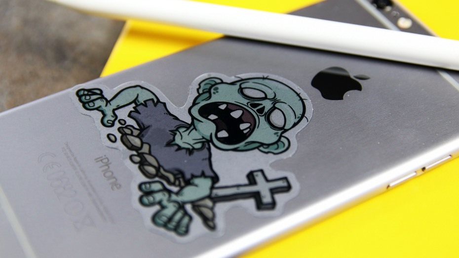 Transparent die cut zombie sticker on a silver phone on top of a yellow notebook