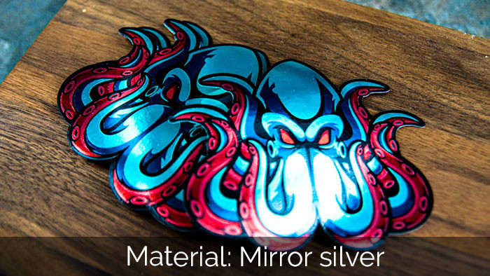 A pile of octopus die cut mirror silver sticker samples  on a wooden block