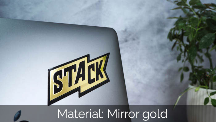 STACK mirror gold logo sticker sample on a space grey Apple MacBook with a green plant in the background