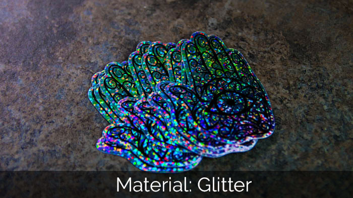 A pile of die cut hand glitter sticker samples on a stone worksurface