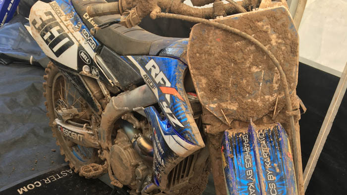 RFX Crescent Yamaha MX bike in a team tent covered in high tack heavy duty stickers and lots of mud on the front number panel