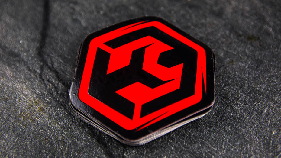 A pile of logo die cut fluorescent red stickers on a work surface