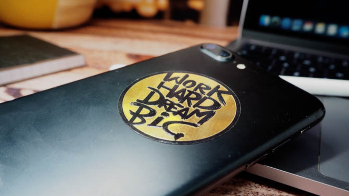 Work hard dream big gold circle sticker applied to a black iPhone