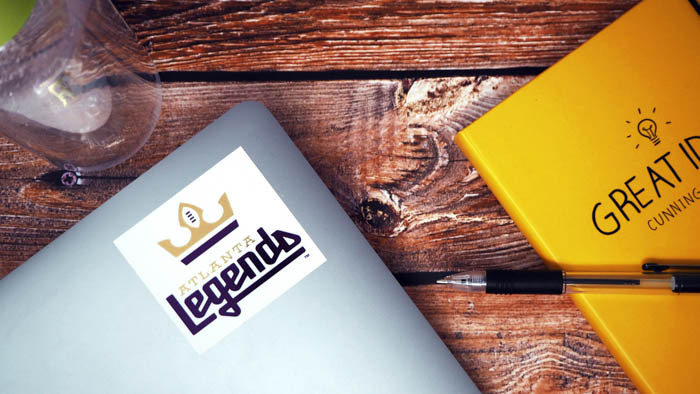 Legends white and gold square sticker applied to a MacBook on a wooden table with a yellow note book