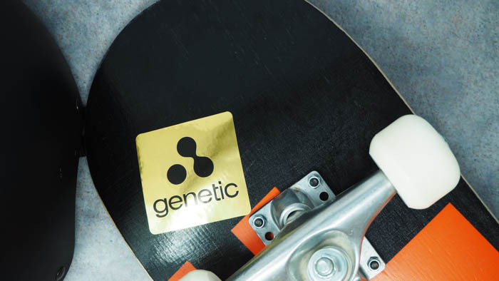 Sticker applied to the underside of a black and orange skateboard with white wheels