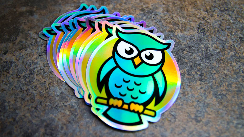A pile of owl die cut holographic stickers on a kitchen counter