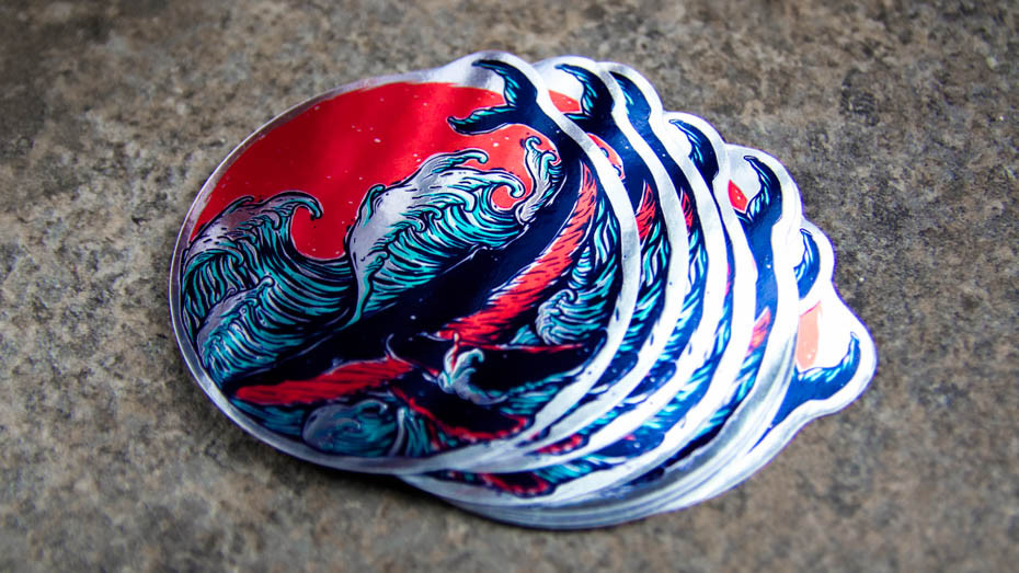 A pile of whale die cut mirror silver stickers on a stone work surface