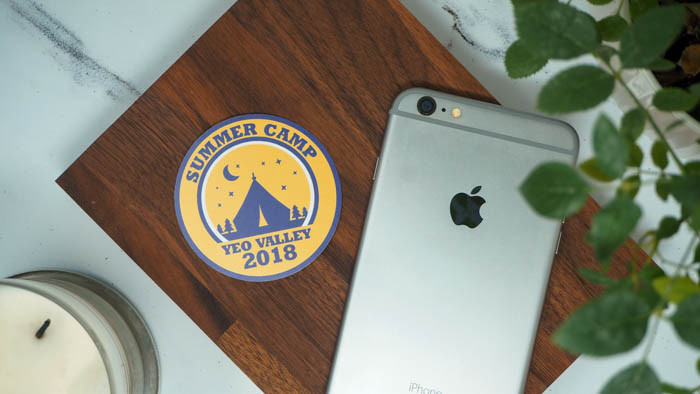 Yellow, blue and white summer camp circular sticker lying next to an iPhone and a candle