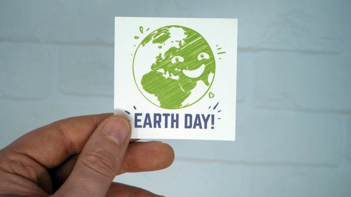 Square earth day sticker being held in someones hand made from biodegradable material which is ecofriendly