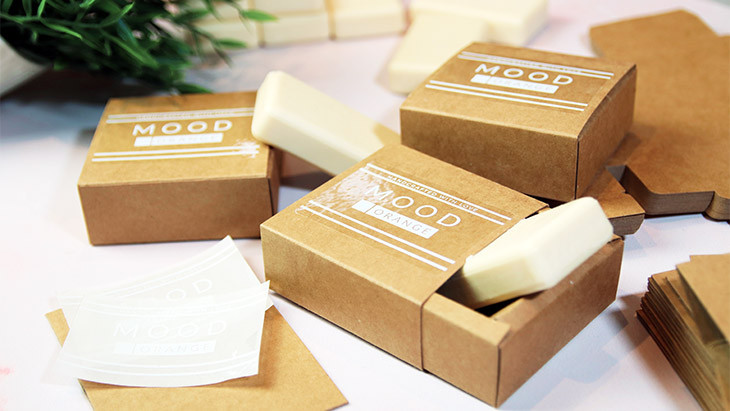 Clear eco-friendly compostable rounded corner stickers applied to soap card box product packaging