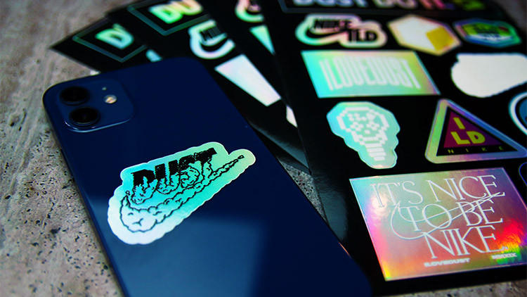 Holographic die cut labels on sheets in full colour on an iPhone  on a stone worktop