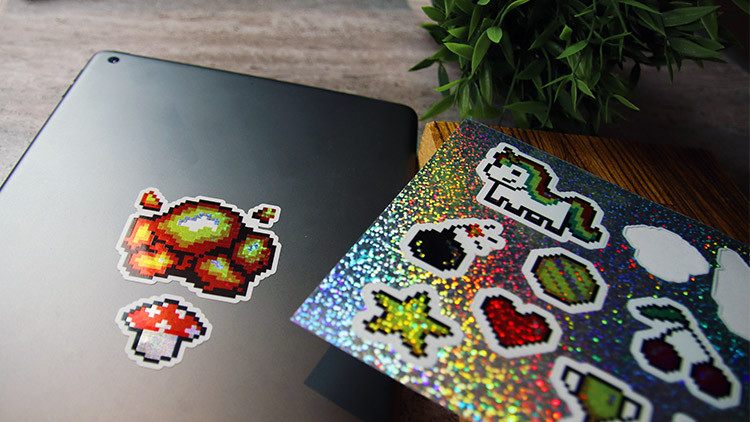 Glitter die cut labels on sheets in full colour on an iPad on a stone table