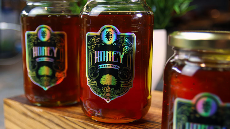 Holographic die cut labels on sheets in full colour on honey jars