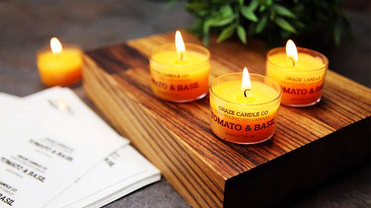 Clear vinyl labels on sheets in full colour on clear candle jars on a wooden block