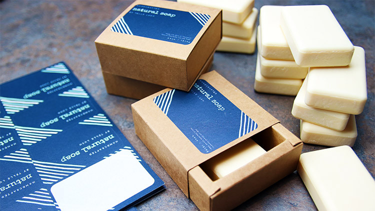 Biodegradable paper labels on sheets in full colour on card soap packaging boxes on a stone surface