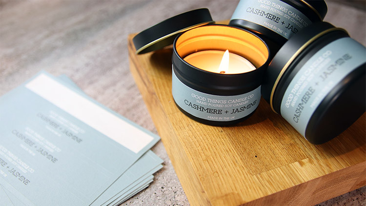 Biodegradable paper labels on sheets in full colour on black candle tins on a wooden block