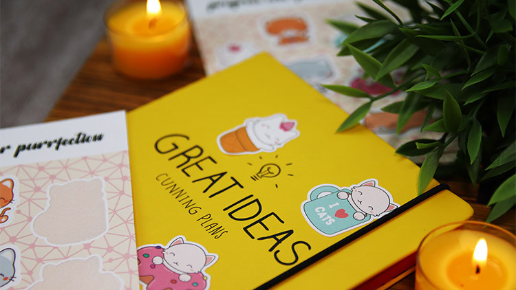 Biodegradable paper labels on sheets in full colour on a yellow notepad with candles on a wooden surface