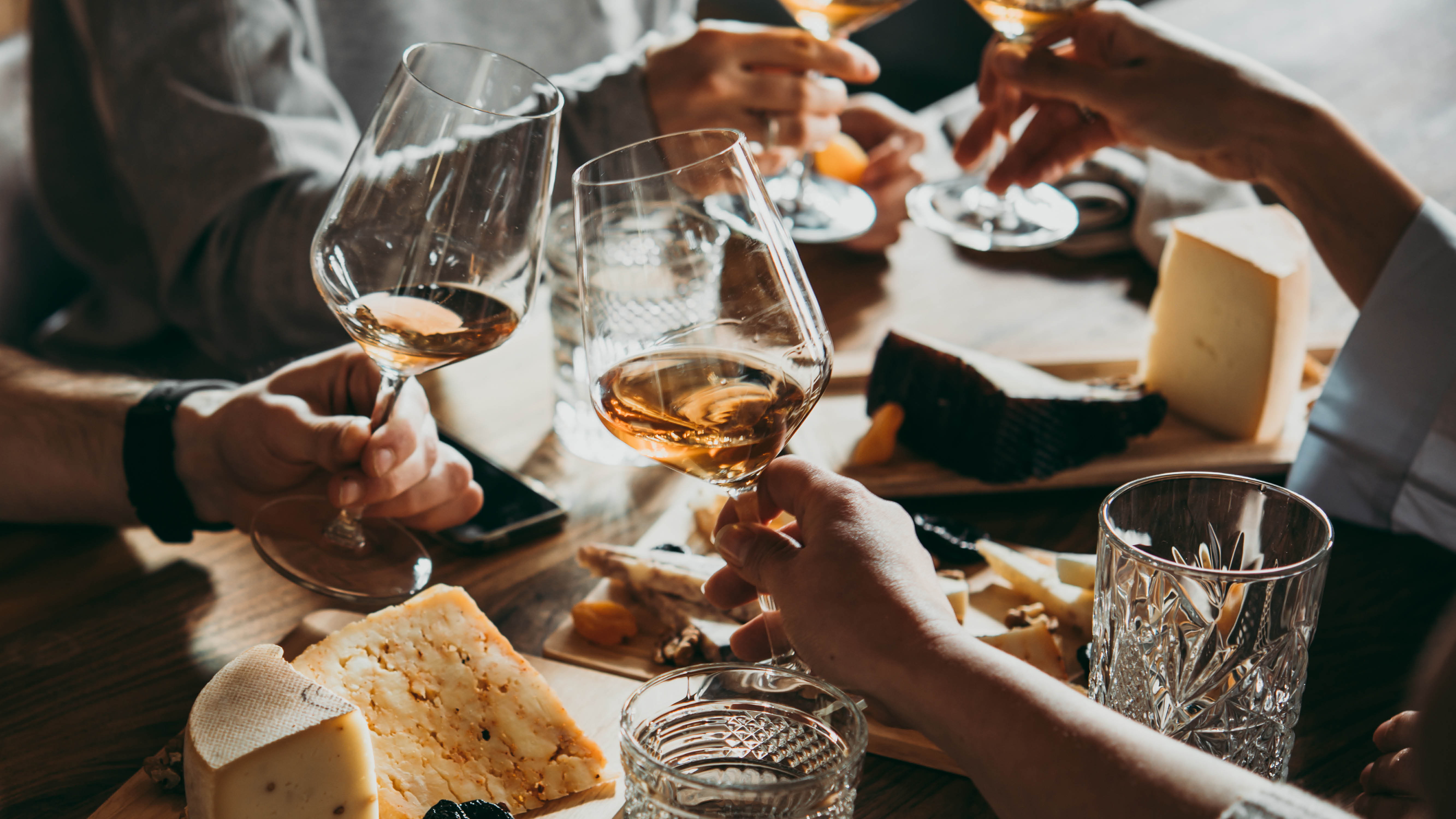 lifestyle-white-wine-glass-toast-over-cheese-board-close-up.jpg