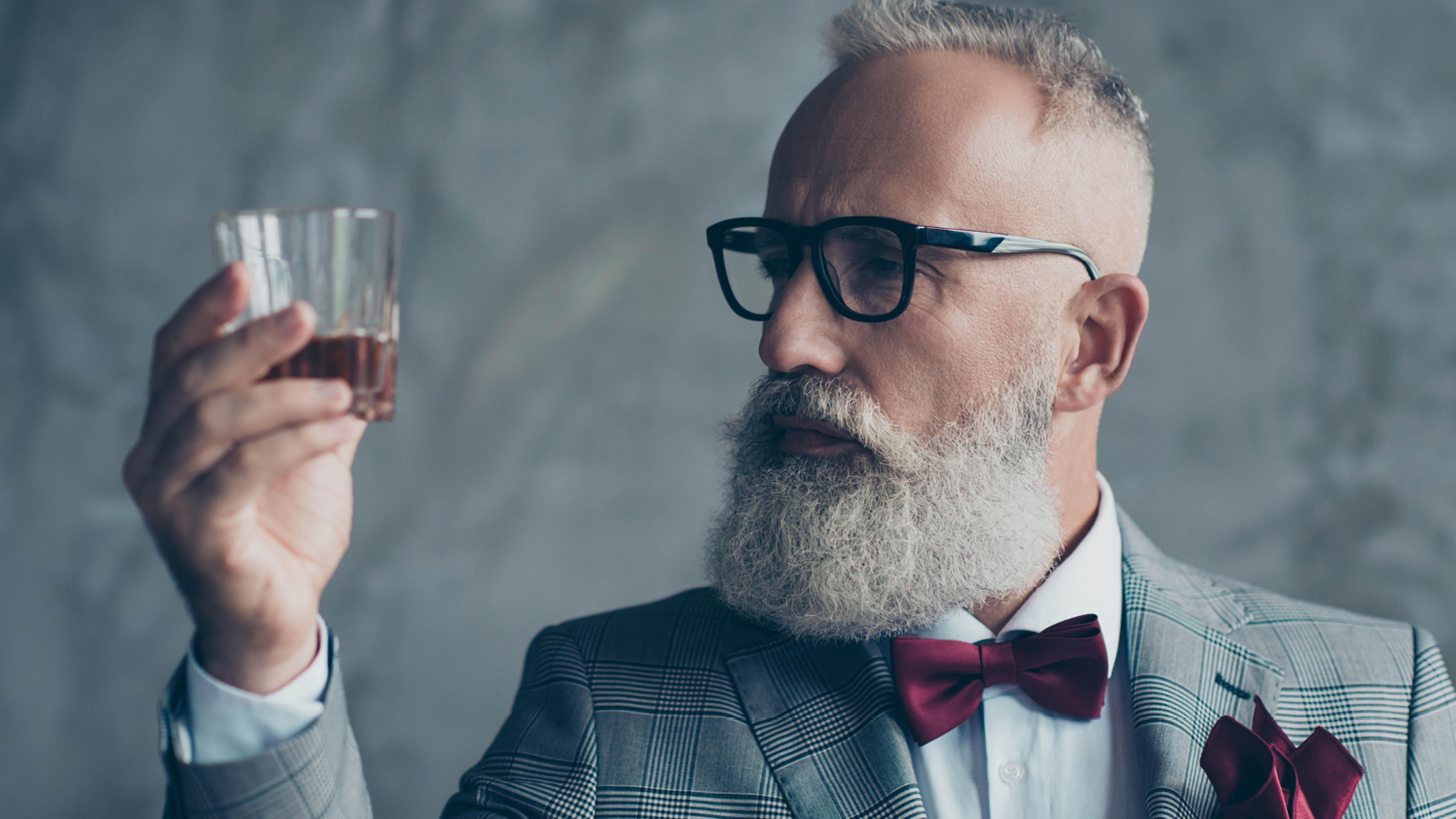 people-older-hipster-gentleman-looking-at-whiskey-glass.jpg