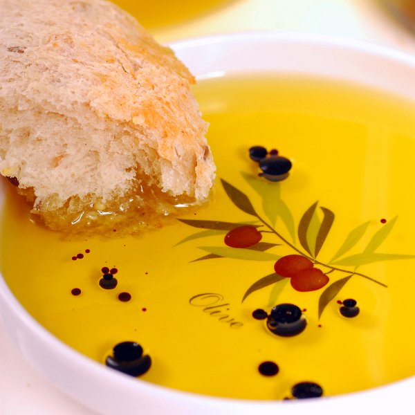 Bread being dipped into delicious olive oil and balsamic vinegar