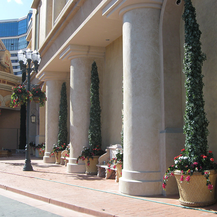 Photo of a white building with thick columns, in between each column there is a matt tall plant with a cone shape.