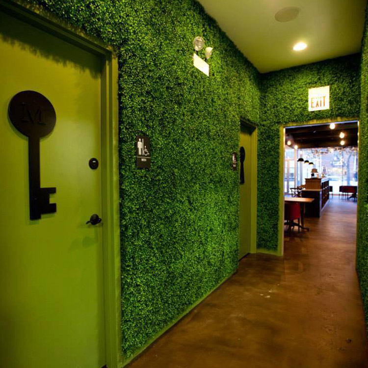 A corridor with walls covered by foliage. There is a door for men bathroom on left side with a black key on it and a door for women bathroom on right side with a black lock on it.