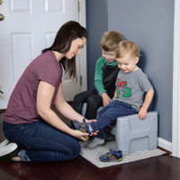 Simplay3 Sibling Step Stool used as a seat for putting on children's shoes.