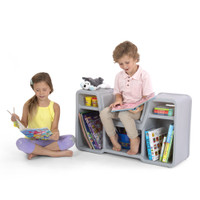 Boy and girl reading books around the cozy cubby reading nook.