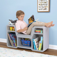 Boy lounging on cozy cubby reading nook enjoying a book.