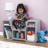 Smiling girl enjoying book on cozy cubby reading nook.