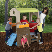 Smiling mom watching kids play on Young Explorers Adventure Playhouse outside!