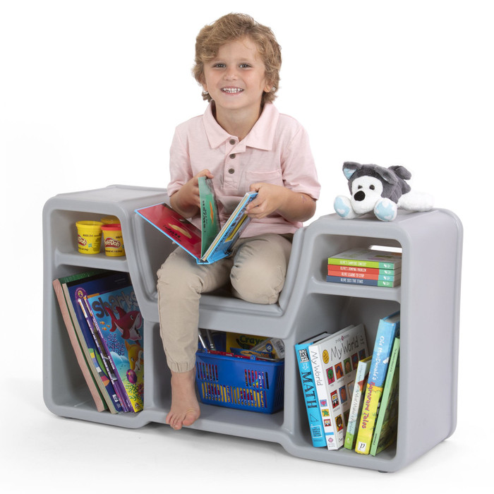 Smiling boy enjoying the cozy cubby reading nook.