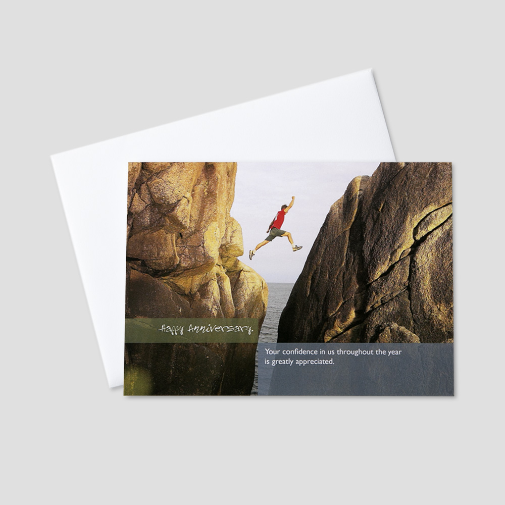 Employee Anniversary greeting card featuring a man achieving great heights between two rock cliffs amidst an anniversary message