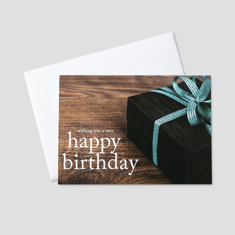 Corporate Birthday greeting card featuring a birthday message next to a present with a bow on a wooden background