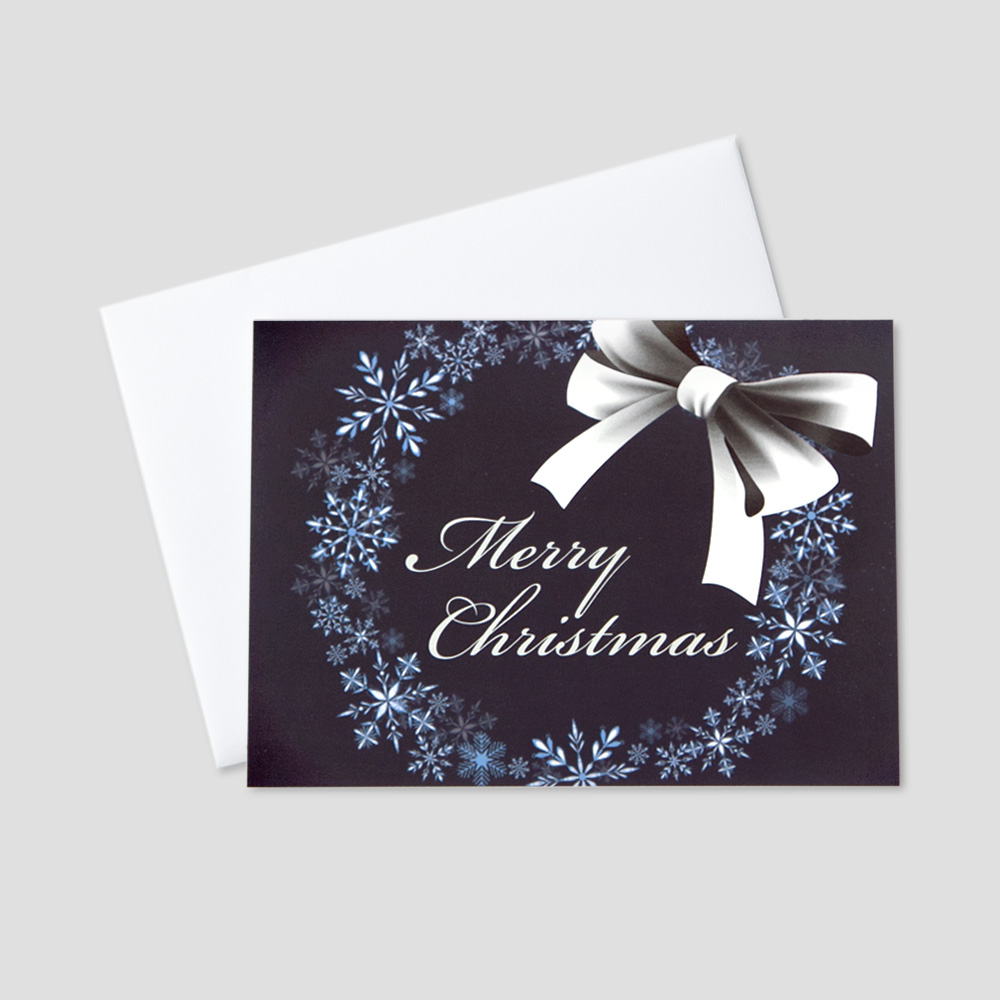 Professional Christmas greeting card featuring Merry Christmas surrounded by a wreath of snowflakes on a navy blue background