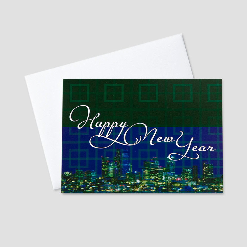 Professional New Year greeting card with an image of a city scape at night and Happy New Year message in a script font