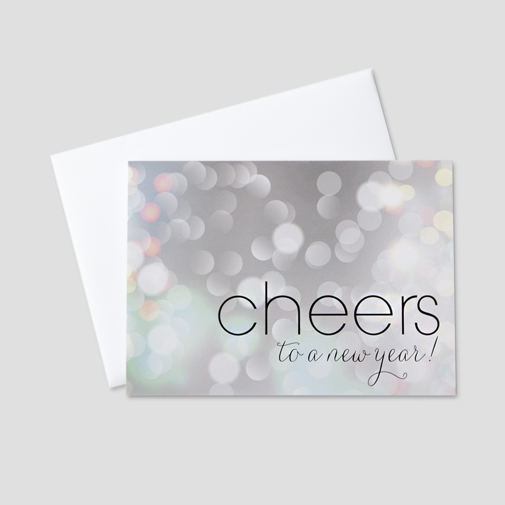 Festive New Year greeting card with cheers to the new year message on a bubbly silver and white background
