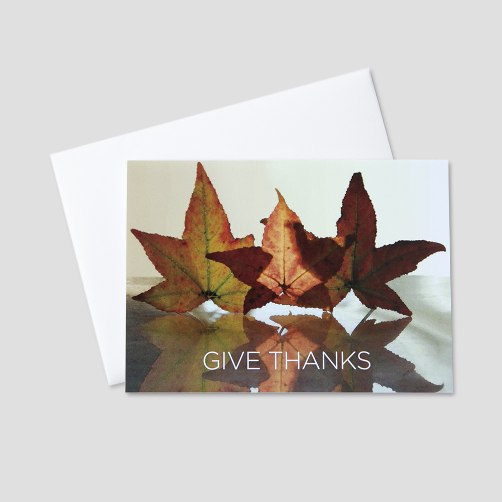 Company Thanksgiving greeting card featuring autumn leaves on a reflective background and a give thanks message