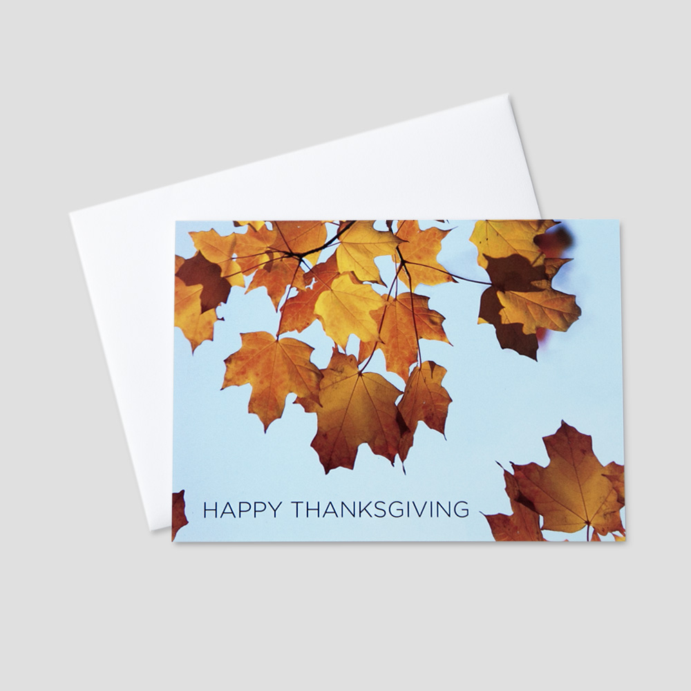 Client Thanksgiving greeting card with a blue sky and autumn leaves on a tree and Happy Thanksgiving in a block font