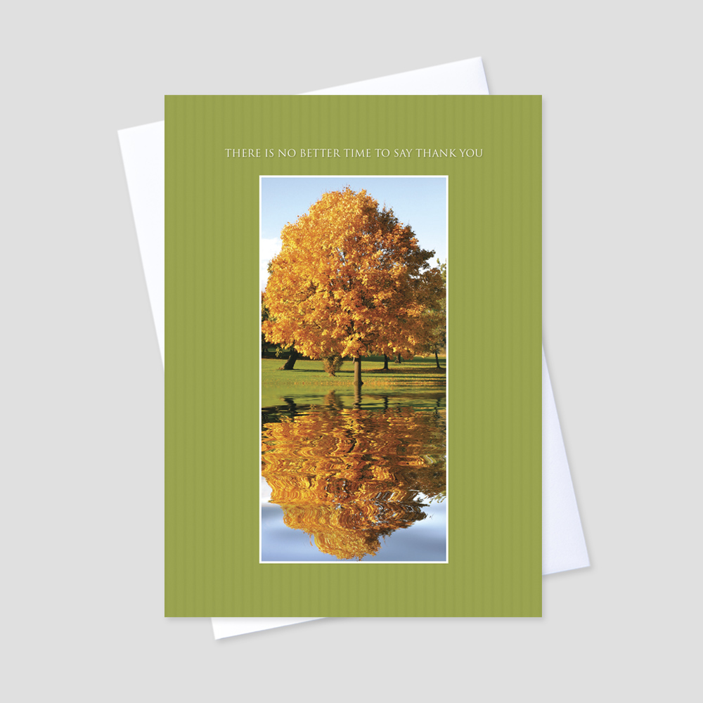 Company Thanksgiving greeting card with a green striped vertical border surrounding a large fall colored tree reflected in a lake
