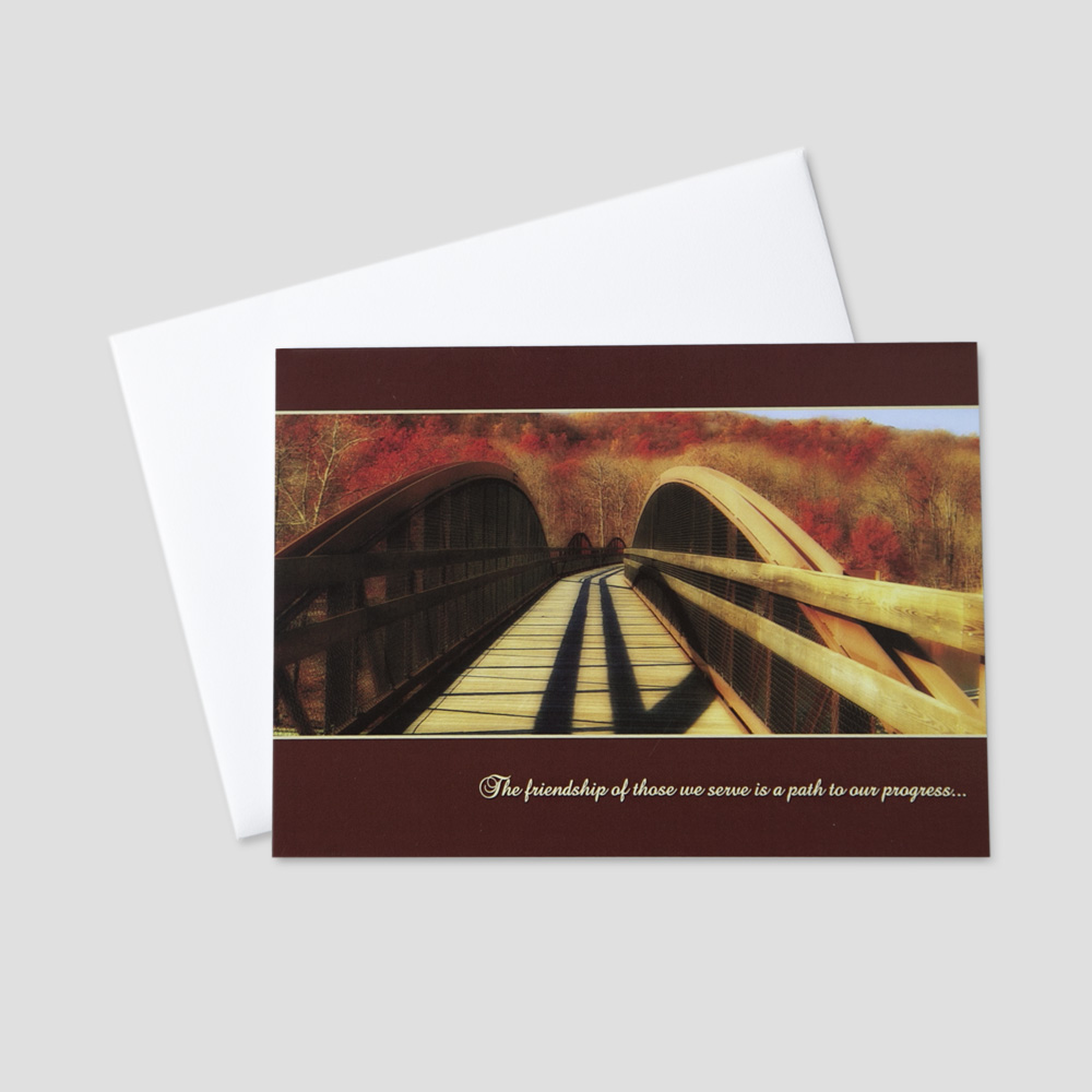 Company Thanksgiving greeting card focused on a bridge through a fall colored mountainside and message of thanks and appreciation
