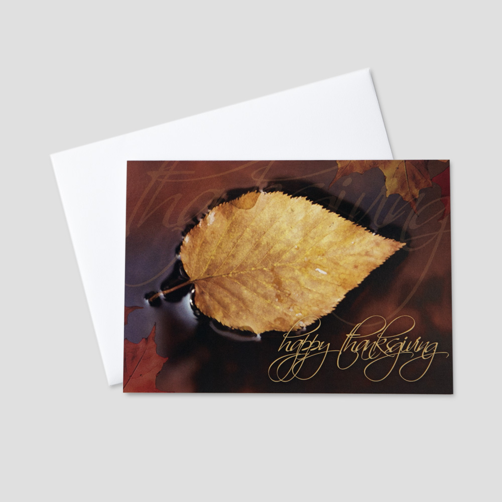 Professional Thanksgiving greeting card with a script Happy Thanksgiving message next to a floating fall colored leaf and brown background